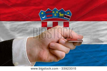 man stretching out credit card to buy goods in front of complete wavy national flag of croatia poster
