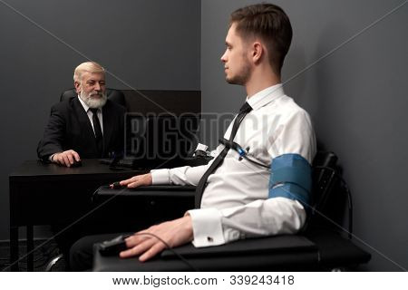 Side View Of Skilled Man In Black Smart Suit Sitting At Table And Asking Question To Patient. Male I