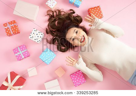 Young Asian Excited Woman Lying On Pink Floor With Many Colorful Gift Boxes. Top View.