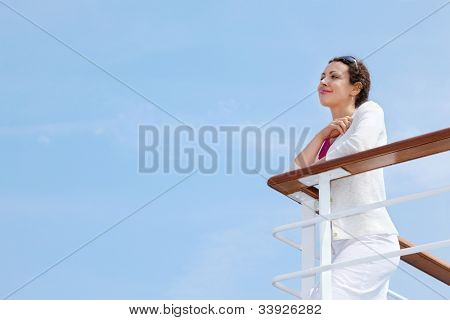 Beautiful happy woman stands on board of large ship and rests her hands on railing