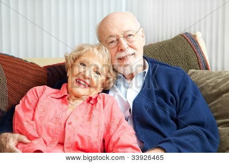 Retired senior couple relaxing together on their living room sofa.