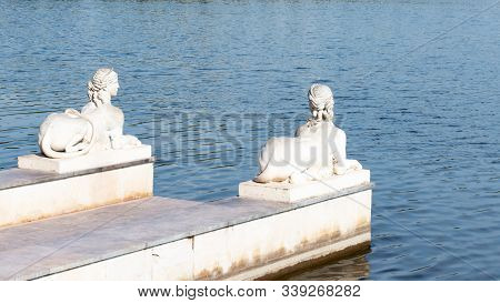 Stone Pier With Plaster Sculptures Pond Lake. Sphinx Sculpture With The Body Of A Lion And The Head