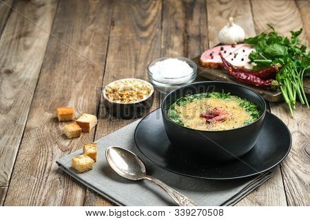 Pea Soup With Bacon, Herbs And Bread Crumbs On A Rustic Background Copy Space.