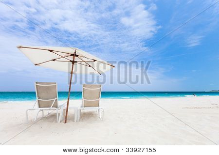 Two chairs under umbrella on beautiful tropical beach in Turks and Caicos