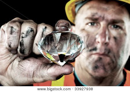 A dirty diamond miner covered in soot shows off a precious gem found in a coal mine.
