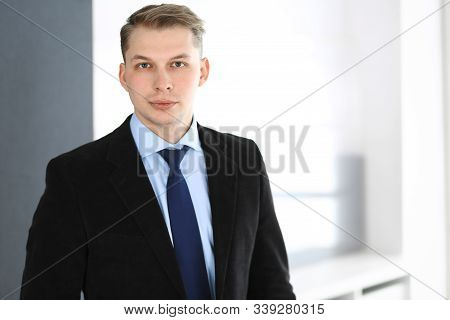 Headshot Of Businessman Standing Straight In Office. Success And Business Workplace Concept