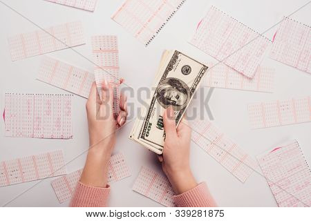Cropped View Of Woman Holding Dollar Banknotes And Lottery Ticket Near Scattered Lottery Cards On Wh