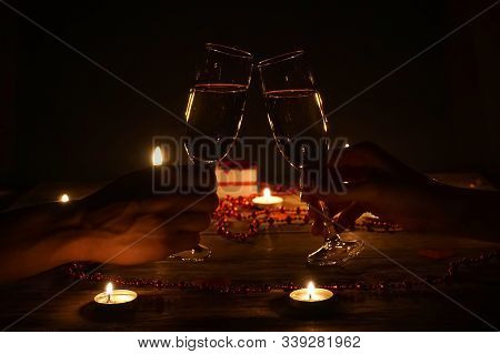 Young Couple With Glasses Of Champagne In Hands Close-up. Romantic Candlelit Dinner At The Table. Co