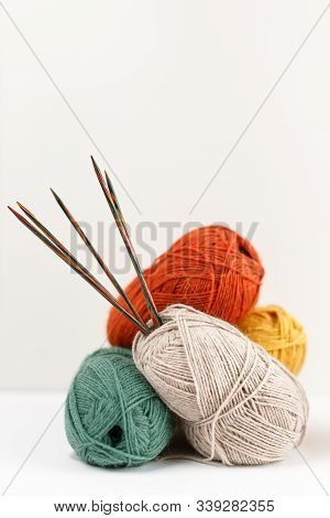 Red, Green, Yellow And Beige Clews Of Yarn Of Pastel Colors. Multicolored Wooden Knitting Needles St