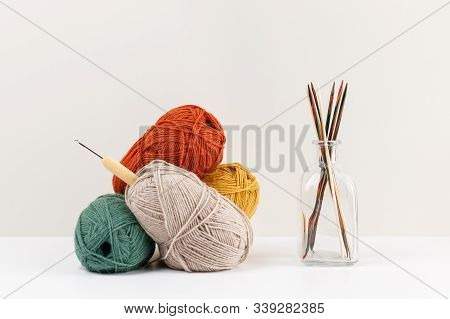 Multicolored Wooden Knitting Needles In Glass Bottle. Red, Green, Yellow And Beige Clews Of Yarn Of