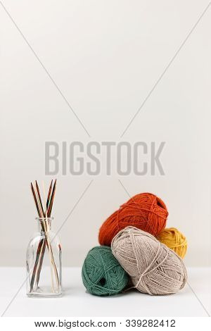Vertical Photo Of Multicolored Wooden Needles In Glass Bottle And Red, Green, Yellow And Beige Paste