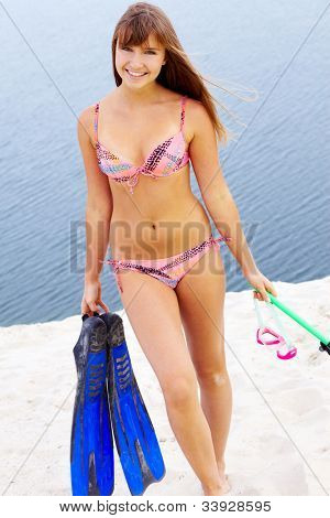 Portrait of teenage girl in bikini carrying scubadiving equipment