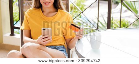 Happy Atractive Woman Holding A Credit Card Buying Online With A Smart Phone