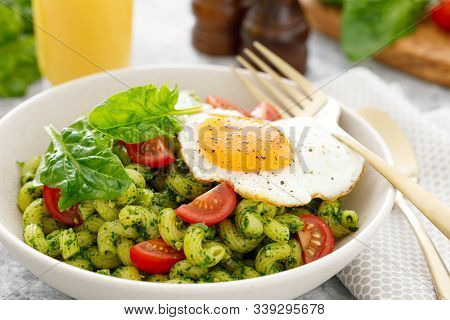 Pasta Cavatappi With Spinach Pesto, Tomatoes And Fried Egg In Bowl Served For Lunch