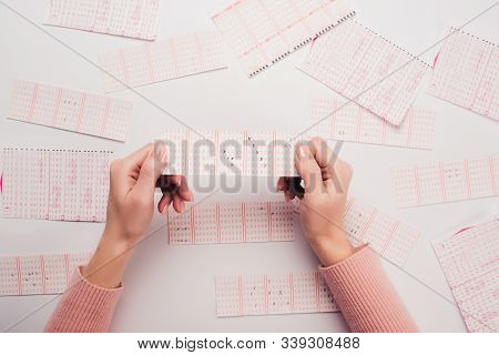 Cropped View Of Woman Holding Lottery Ticket With Marked Numbers Near Scattered Lottery Cards On Whi