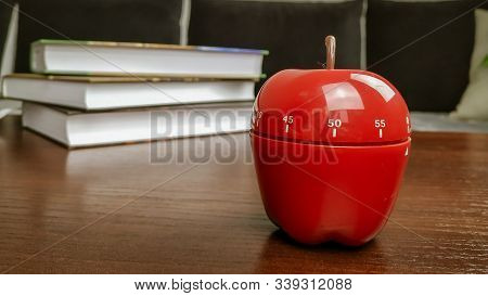 Studying With Pomodoro Technique With A Kitchen Timer In A Shape Of An Apple For Timing The Study Se