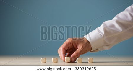 Hand Of A Businessman Placing Five Blank Wooden Dices In A Row