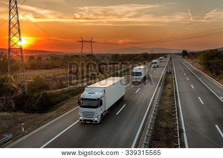 Convoy Of Blue Lorry Trucks On A Country Highway Under Amazing Orange Sunset Sky. Highway Transporta