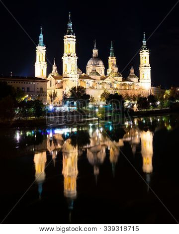 Night View Of The Basilica Of Our Lady Of The Pillar Reflected In The Ebro River In Zaragoza