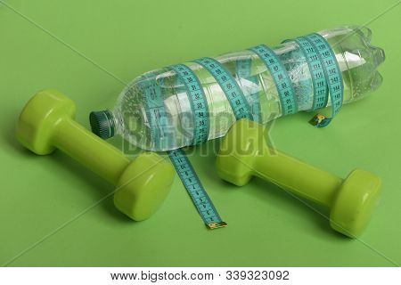 Sports Regime Equipment. Dumbbells In Green Color And Water Bottle