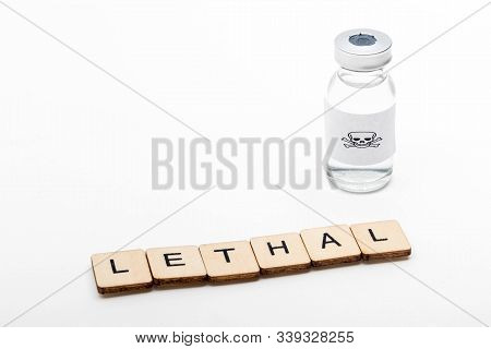 A Glass Medical Vial With A Skull And Crossbones On A White Background With A Sign Reading Lethal