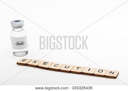 A Glass Medical Vial With A Skull And Crossbones On A White Background With A Sign Reading Execution