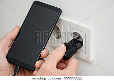 A Person Is Inserting A Plug Into An Electrical Outlet To Charge A Smartphone.