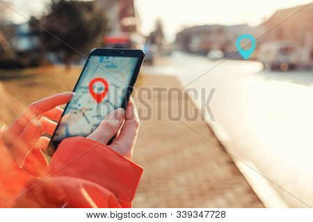 Concept Of Internet Maps And Navigation. Female Hands Hold Smartphone With Maps App, And Marked Loca