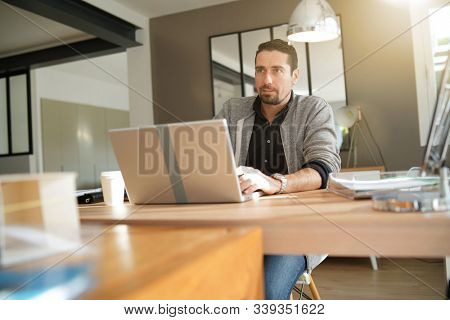 Businessman working late on laptop in co-working offices