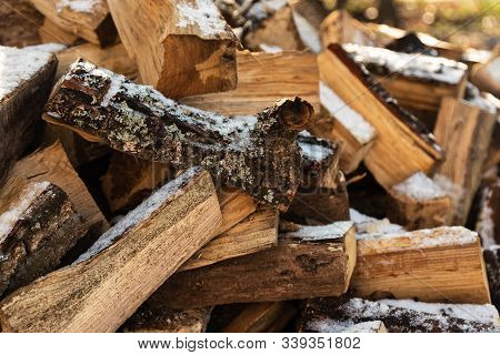 Firewood Stacked In Winter. Wood Pile With Snow Stacked For Firewood. Chopped Stock Of Firewood Unde
