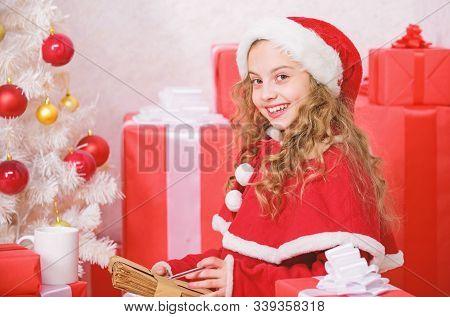 Letter For Santa. Wish List. Girl Little Kid Hold Pen And Paper Near Christmas Tree Writing Letter.