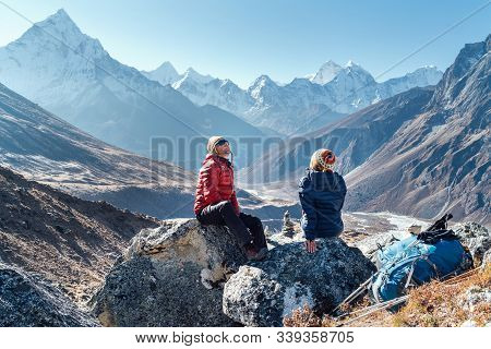 Cute Couple Resting On The Everest Base Camp Trekking Route Near Dughla 4620m. Man And Woman Enjoyin