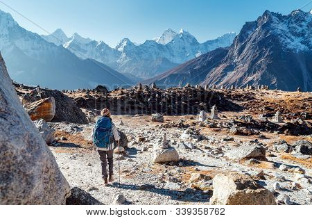 Young Female Backpacker Following Everest Base Camp Trekking Route Using Trekking Poles And Enjoying