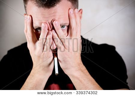 Secret Smoker With A Cigarette In His Mouth Shamely Covers His Face With His Hands And Looks Through