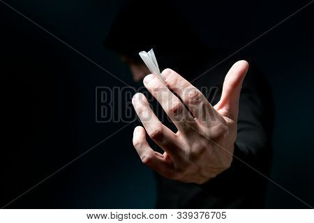 Dark Silhouette Of A Man Holds Out His Hand A Frame With A Dose Of The Drug In The Package. Dose Of