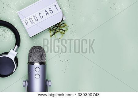 Top View Photo Of Podcast Concept - Lightbox With Letters Podcast On It, Headphones And Professional