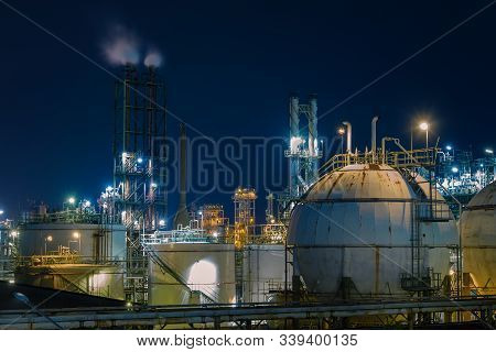 Gas Storage Sphere Tanks In Petrochemical Plant At Night, Glitter Lighting Of Petrochemical Plant