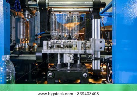 The Production Of Pet Bottles In The Automatic Blowing Machine For Drinking Water Factory. The Opera