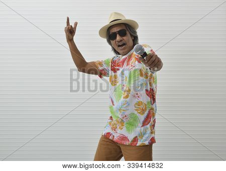Happy Elderly Traveler Asian Man Wearing Summer Shirt, Straw Hat And Sunglasses Singing Karaoke With