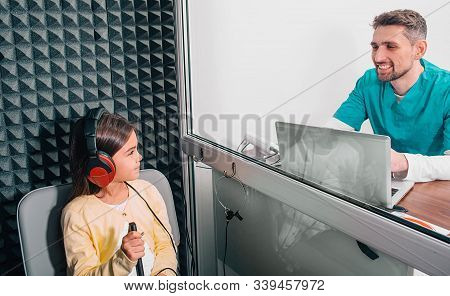 Cute Mixed Race Girl Having A Hearing Test In A Special Room, She Is Wearing Headphones, Her Audiolo