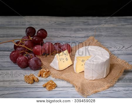 Soft Blue Cheese, Ripe Red Grapes And Walnuts On Natural Backdrop. A Wedge Of Full Fat Soft Blue Che