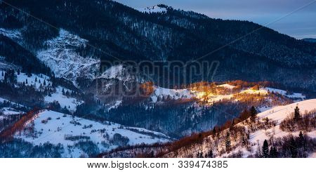 Winter Countryside Scenery At Dawn. Landscape With Spot Of First Light On Snow Covered Hill. Dark Co