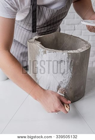 Pottery Workshop. Male Ceramist Painting A Pot With A White Paint
