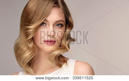 Woman With Curly Beautiful Hair  On Gray Background. Girl With Beauty A Pleasant Smile. Short Wavy