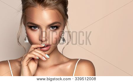 Beautiful Girl With Earrings  .   Woman In  Jewelry And Manicure On Nails  . Beauty  ,   Cosmetology