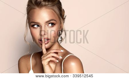 Beautiful Girl With Earrings Makes A Secret Sign .   Woman In  Jewelry And Manicure On Nails  . Beau