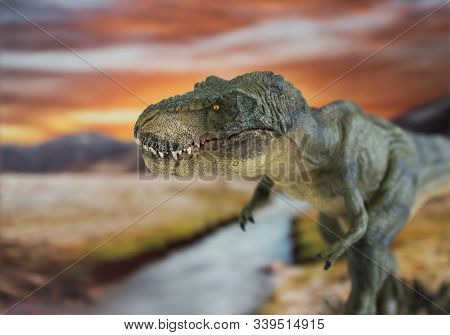 Portrait Of Walking And Dangerous Tyrannosaurus Rex With River In The Background. Lateral View