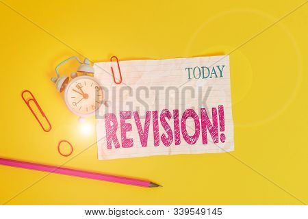 Word writing text Revision. Business concept for action of revising over someone like auditing or accounting Alarm clock clips crushed note rubber band pencil colored background. poster