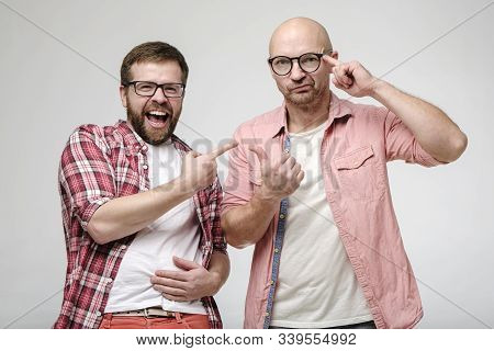 Man Laughs Out Loud, Points A Finger At Another Person Who Makes A Hand Gesture And Looks At The Cam