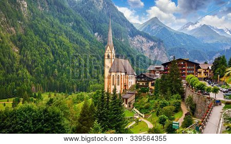 Heiligenblut, Austria. Panoramic aerial view of Saint Vincent Church, famous tourist attraction in East Tyrol region in Alps. Grossglockner Mountain landscape with high snowbound summits.
